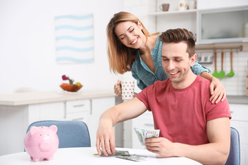Young couple with money at home