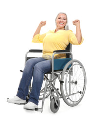 Mature woman in wheelchair on white background
