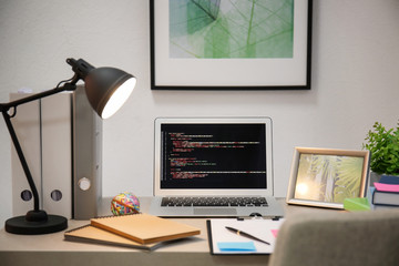 Comfortable workplace with laptop on desk at home