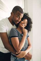 Young black couple embracing at home