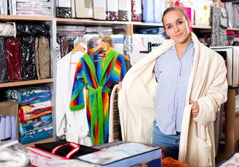 Girl customer deciding on the choice of bathrobe