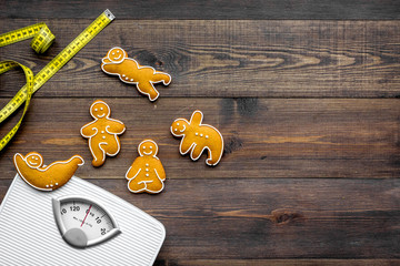 Yoga for lose weight. Scale, measuring tape and cookies in shape of yoga asans on dark wooden background top view copy space