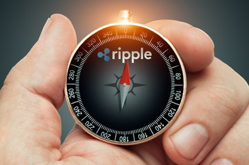 hand holding compass and needle pointing ripple coin logo