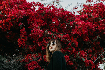 Young Woman Wearing Big, Round Sunglasses in Front of Red Flowers