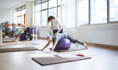 Senior Woman Doing Exercise With Pilates Ball