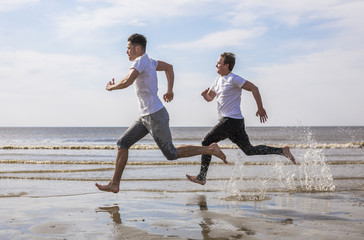 Young men having a running competition on the beach.
