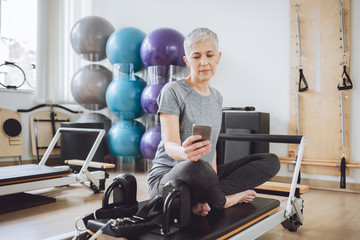 Senior Woman Using Cell Phone at Gym