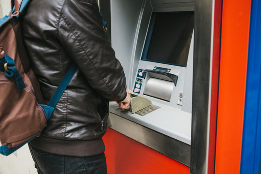 The tourist withdraws money from the ATM for further travel. Dials the code with one hand and closes the buttons with the other hand to protect the information.