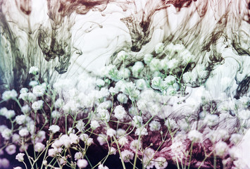 Multiple exposure of white flowers and colorful ink swirls
