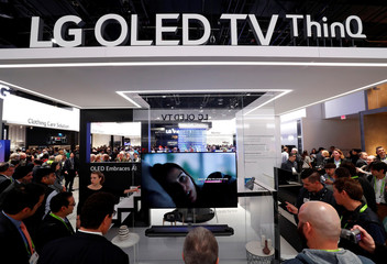 People look over a display of OLED ThinQ televisions in the LG Electronics booth at the Las Vegas Convention Center during the 2018 CES in Las Vegas