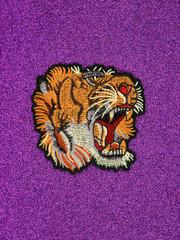 A vintage tiger patch on a glitter ultra violet background