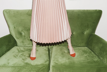 Low section of a woman in pink skirt standing on sofa