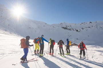 Group of skiers ski touring on snow-capped mountain plateau