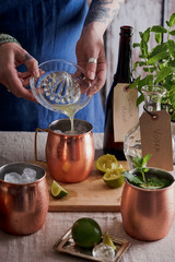 Woman adding freshly squeezed lime juice to a Moscow mule cocktail.