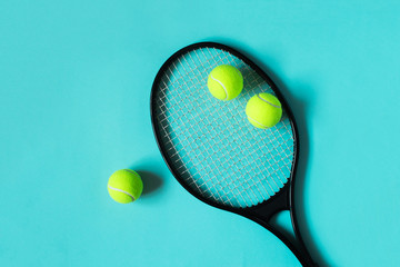 Tennis balls and racket on blue background. Sport equipment. Flat lay.