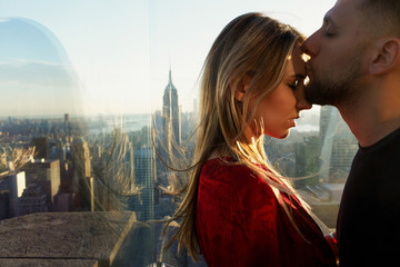 Man kisses woman tender standing before a great view on New York behind the window