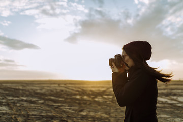 Woman taking pictures in the desert during sunset