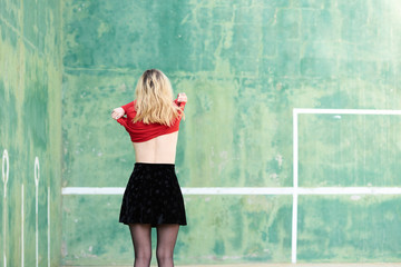 Woman taking off clothes at wall