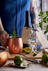 Woman with her hand on a copper mug,making Moscow mule cocktails.
