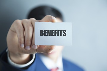 BENEFITS word on business card held by a man