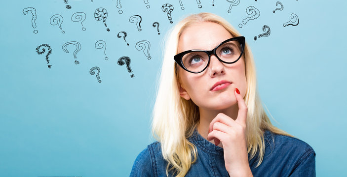 Young woman in a thoughtful pose with question marks