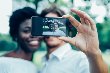 Smiling mix-raced couple taking selfie with phone