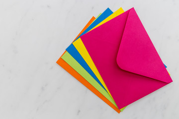 Colorful envelopes on white marble background