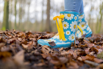 Child's wearing sky blue wellies with daisy patterns playing in a forest in autum leaves on a bright cold morning