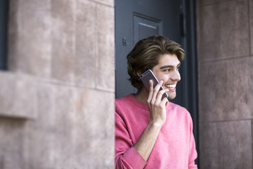A young man in pink shirt using a cellphone.