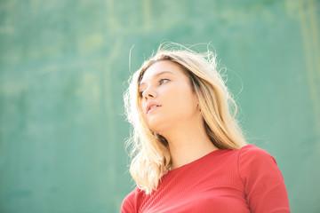 Beautiful woman standing at green wall