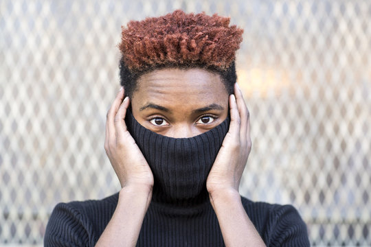 Young black man hiding in a black turtleneck.