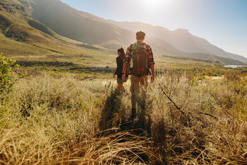 Couple walking through countryside hiking trail