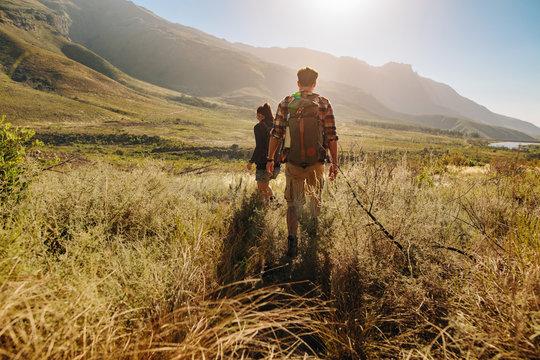 Couple walking through countryside hiking trail
