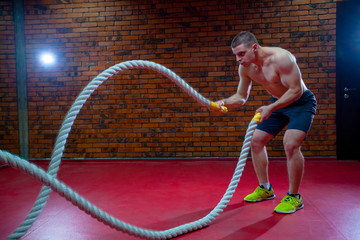 Muscular Shirtless Man in a Gym Exercises with Battle Ropes During His Fitness Workout High-Intensity Interval Training.