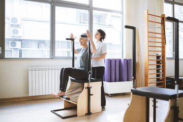 Woman Doing Back Exercise With Therapist