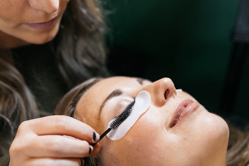 Young woman getting lash extension cosmetology laying down in small business studio