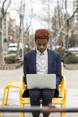 A young black man in a blue suit on a laptop.