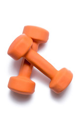 Two orange dumbbells lie on top of each other on a white background