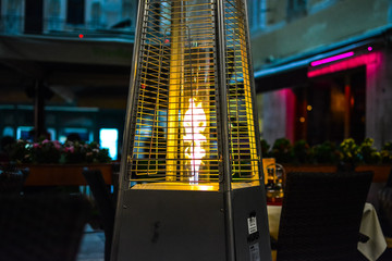 The flame from a patio heater warms a small outdoor, sidewalk cafe late at night in Split Croatia