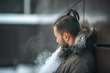 Vape man. Portrait of a handsome young white guy with modern haircut vaping an electronic cigarette opposite the futuristic urban background. Lifestyle.
