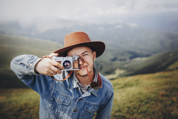 stylish man traveler in hat with photo camera smiling on top of mountain. stylish hipster taking photo. space for text. atmospheric moment. wanderlust and travel concept