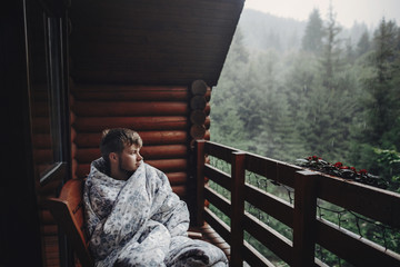 stylish man traveler in blanket relaxing on porch of wooden cabin in rainy day on background of woods in mountains. stylish hipster resting. space for text. atmospheric moment Fotobehang