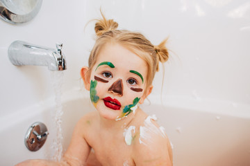 Toddler girl with sad clown face paint in the bath.