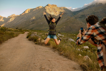 Hiking trip memories, man taking photographs of his excited girl