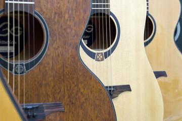 Spoed Foto op Canvas Muziekwinkel Acoustic guitars hang on the wall in a row. Soft focus.