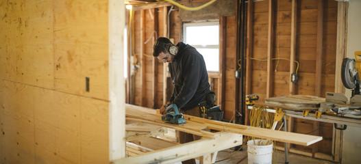 Panoramic  of young carpenter measuring wood cut
