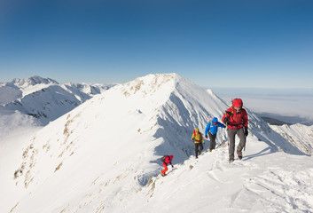 Group of hikers ascending on snow-capped mountain peak