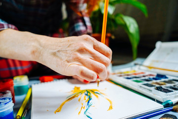 woman draws in yellow paints and pencils on canvas