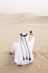 Man in abaya taking photos of the desert