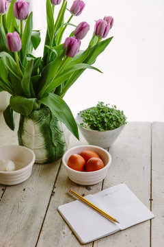 Kitchen counter, with black shopping list, spring flowers and kitchen essentials.